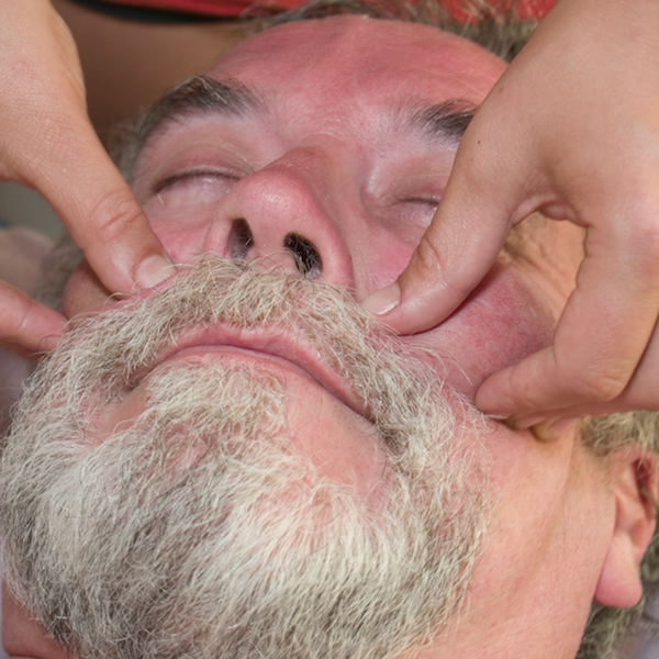 Man in his 50's on a massage table receiving facial massage.