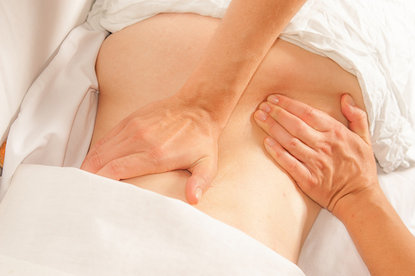 A physio gives myotherapy using trigger points on athlete woman