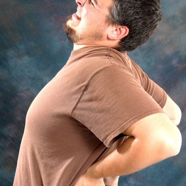 Man with back pain massages his back trying to relieve his backache.