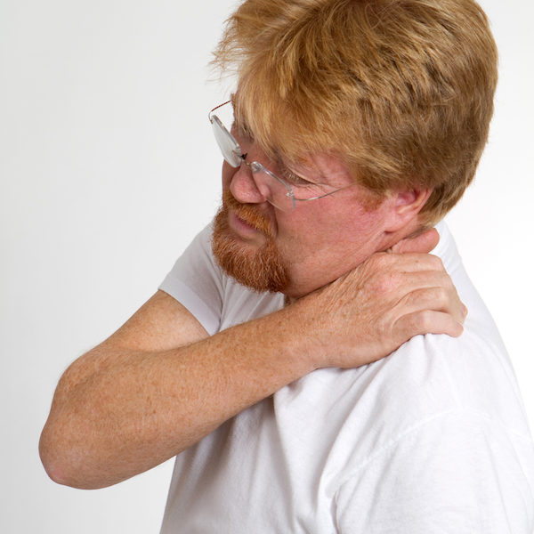 Mature man massages and squeezes his shoulder in pain.